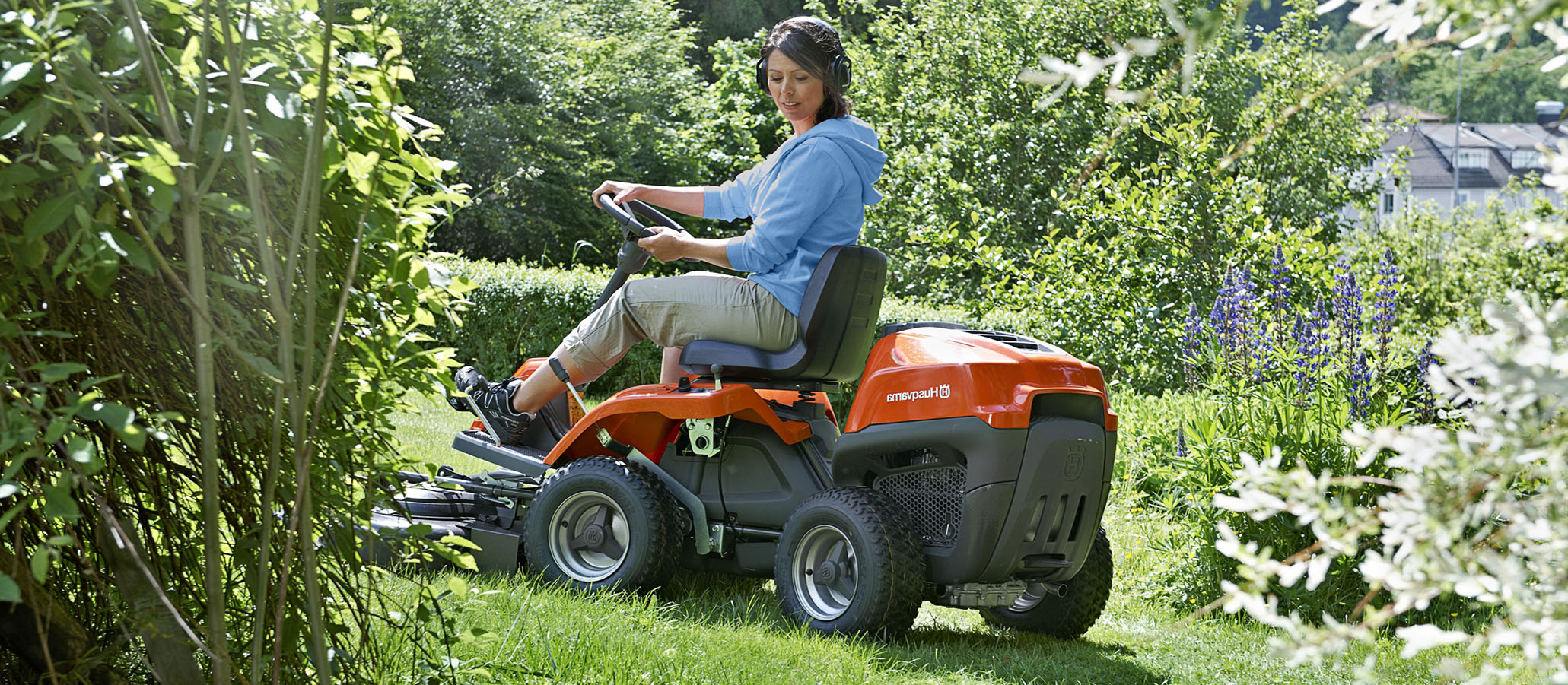 Kvinna på åkgräsklippare i trädgård
