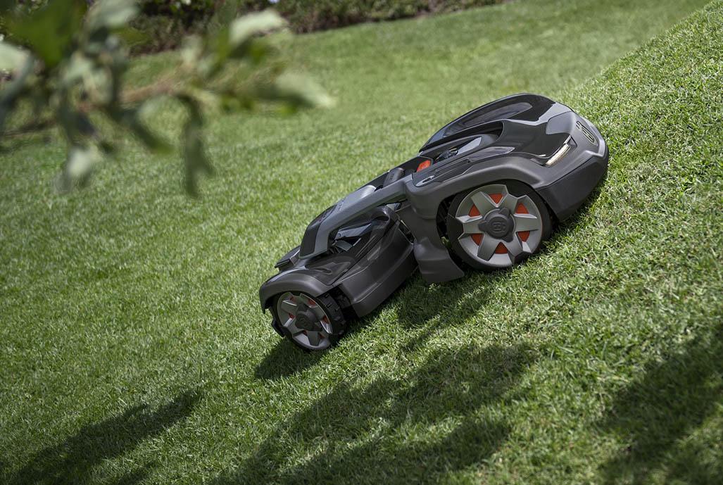 Svart robotgräsklippare i trädgård
